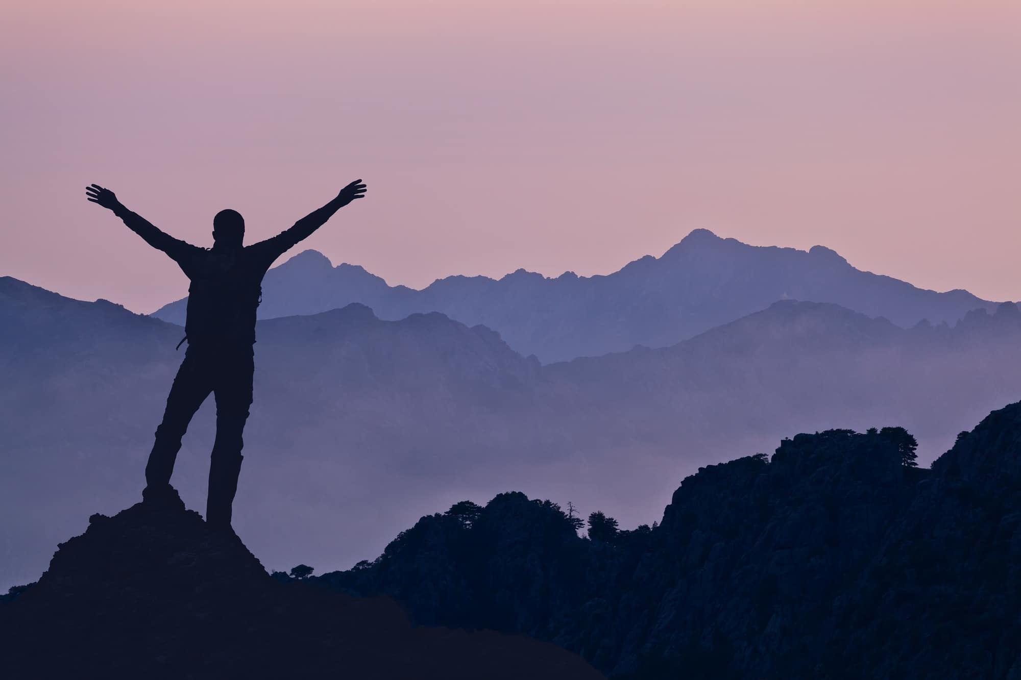 person with outstretched arms on mountain