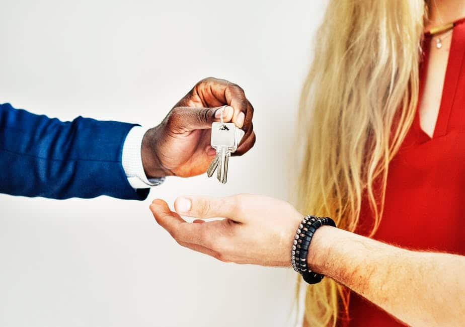 person handing house keys to another person